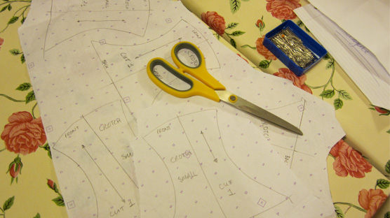 Cutting out pattern pieces from dot and cross pattern paper.