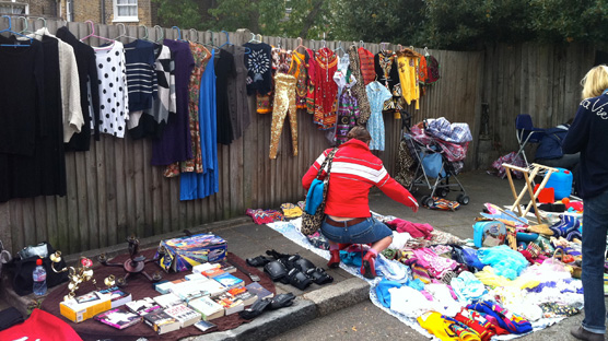 Fences lined with cute and colourful clothing & blankets piled high to rfile through.