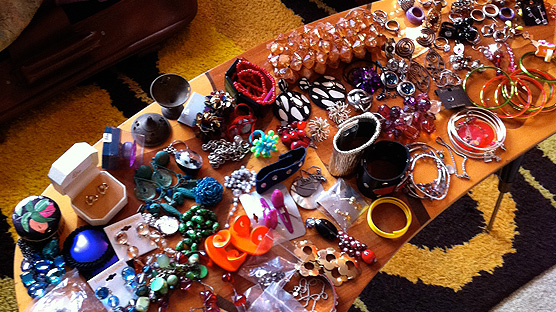 A kidney shaped coffee table filled with fun junk jewellery.