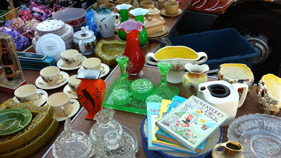 A table heaving with lovely bits of crockery, glassware & annuals.