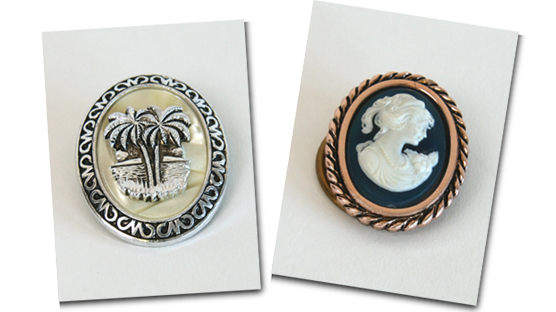 A pair of scarf clips featuring a palm tree and a cameo.